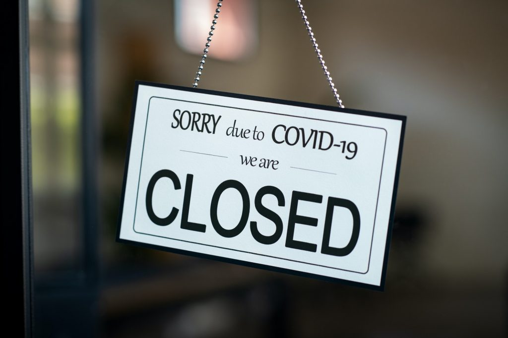 Closed sign hanging on door of cafe due to Covid-19